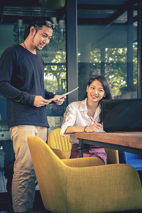 Homem asiático e mulher autônomos mais novos que trabalham com cara de sorriso fotografia de stock royalty free