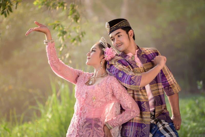 Homem asiático e mulher muçulmanos que vestem o vestido tradicional fotos de stock