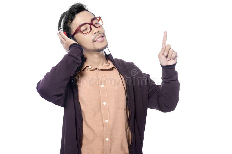 Homem asiático feliz na música de escuta do revestimento marrom com os fones de ouvido em sua cabeça e para apreciar a música foto de stock