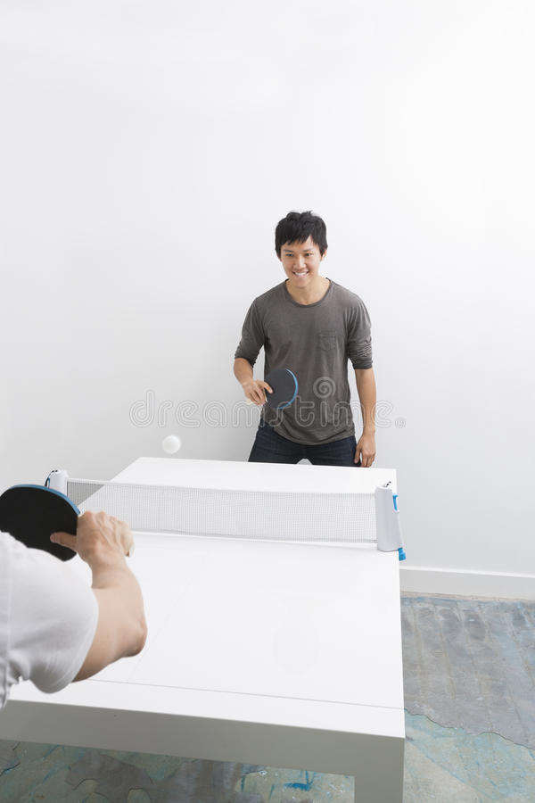 Homem asiático feliz que joga o pong do sibilo com amigo fotografia de stock royalty free
