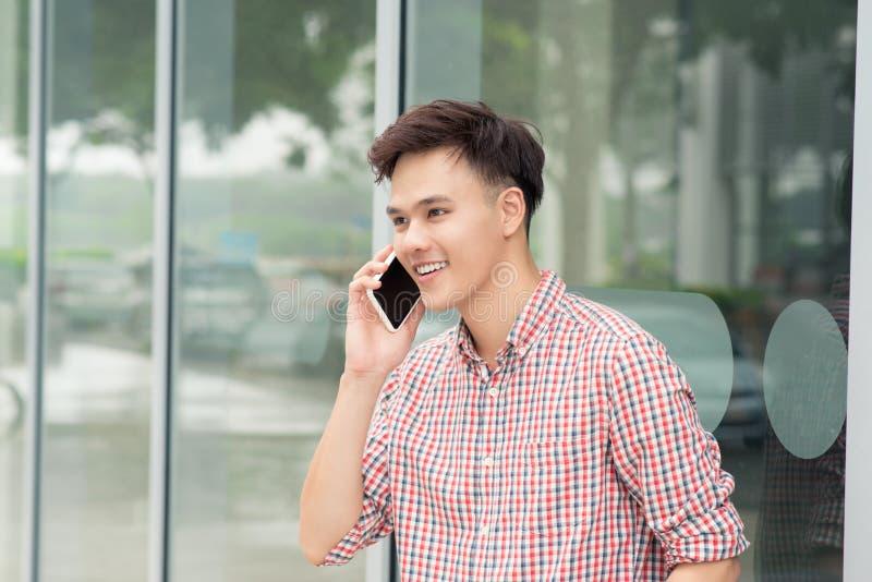 Homem asiático feliz que sorri como falando no outsi ereto do telefone esperto foto de stock royalty free