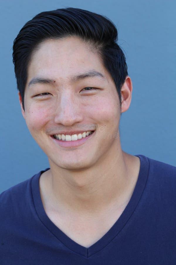 Homem asiático feliz que sorri sobre o fundo azul imagens de stock royalty free