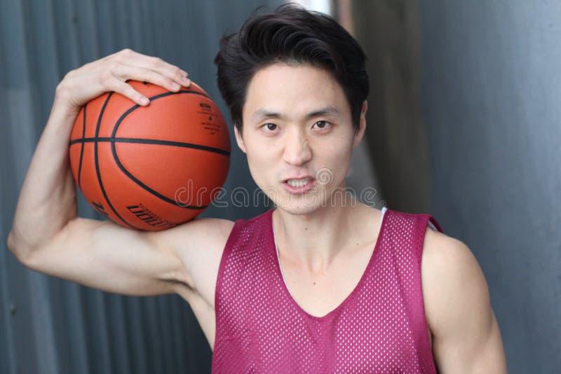 Homem asiático intenso novo que guarda o basquetebol fotografia de stock royalty free