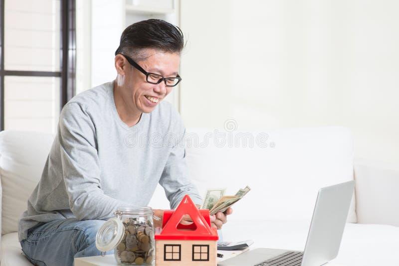 Homem asiático maduro que conta no dinheiro fotografia de stock royalty free
