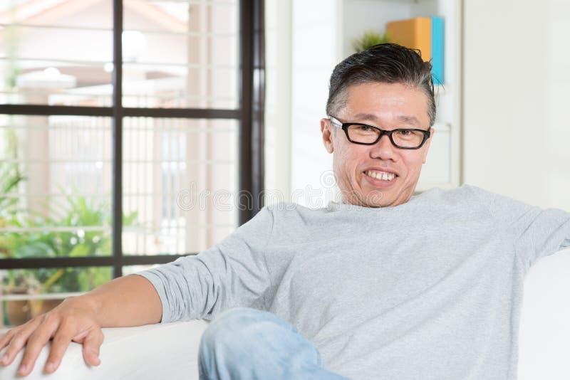 Homem asiático maduro que senta-se em casa fotografia de stock
