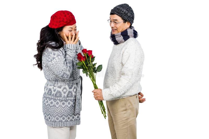 Homem asiático mais idoso que dá a sua esposa flores foto de stock