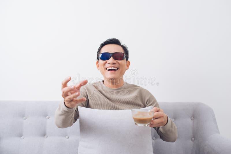 Homem asiático nos vidros 3d que sentam-se no sofá e no filme de observação foto de stock royalty free