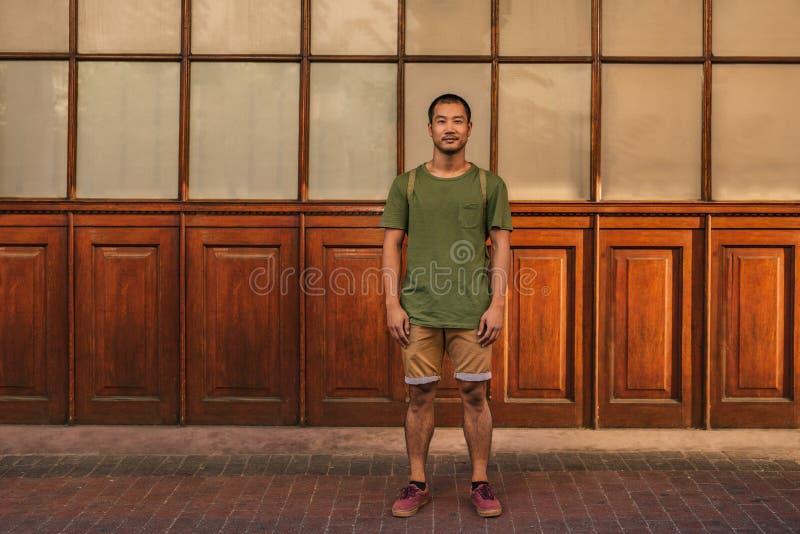 Homem asiático novo à moda que está em uma rua da cidade imagem de stock royalty free