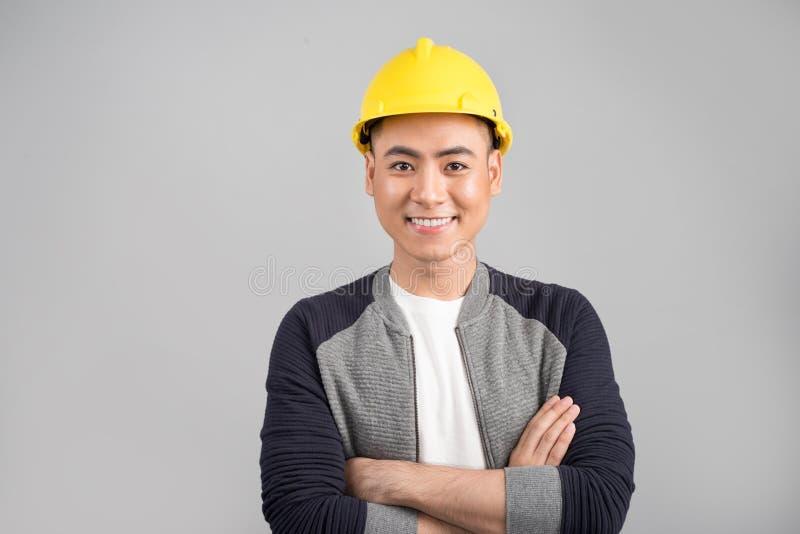 Homem asiático novo com o capacete da construção que olha à câmera imagens de stock