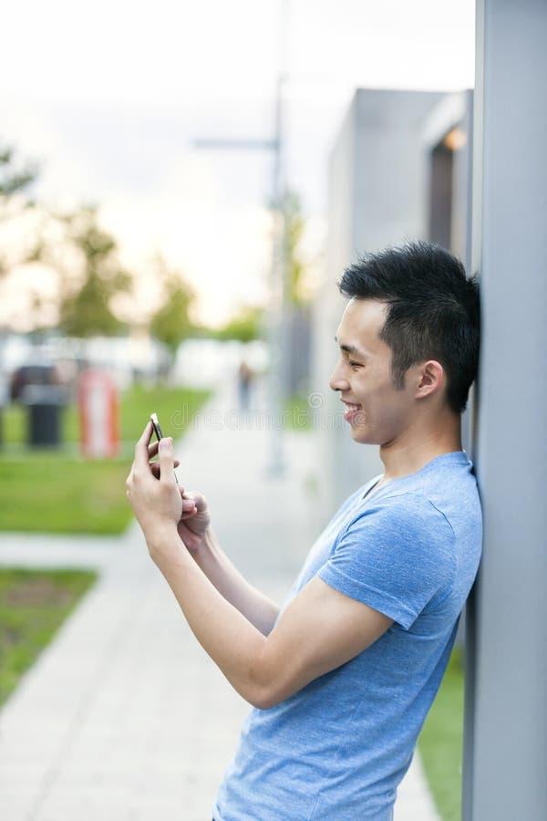 Homem asiático novo com telefone celular fotografia de stock