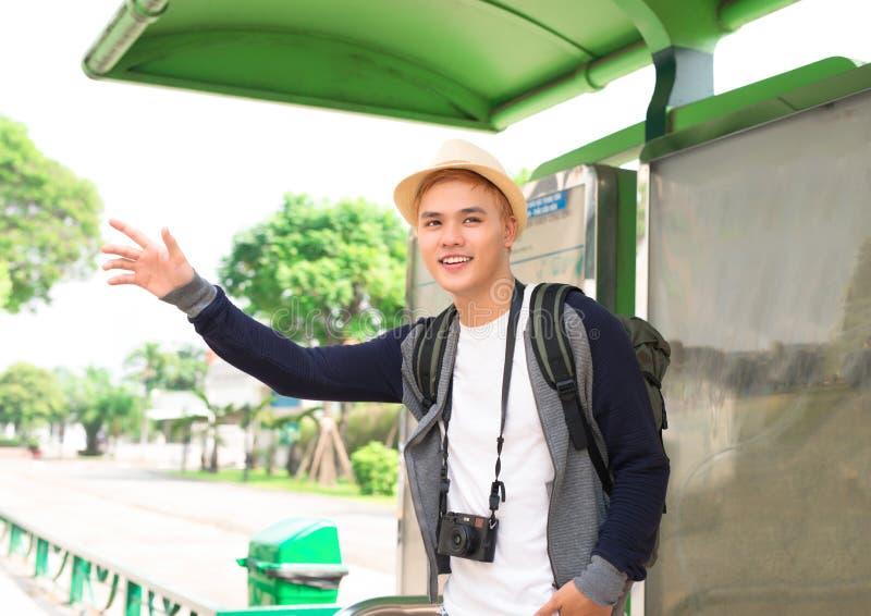 Homem asiático novo considerável que espera seus ônibus e sorriso imagem de stock royalty free