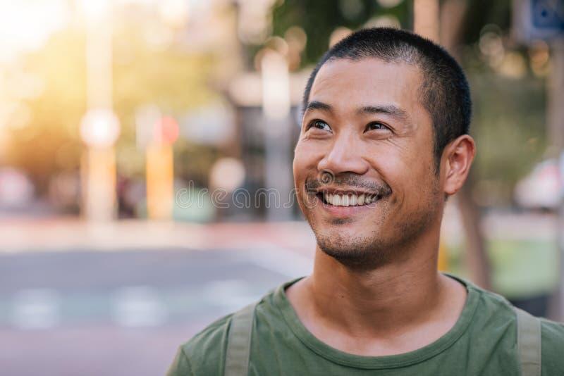 Homem asiático novo considerável que está em um sorriso da rua da cidade imagem de stock