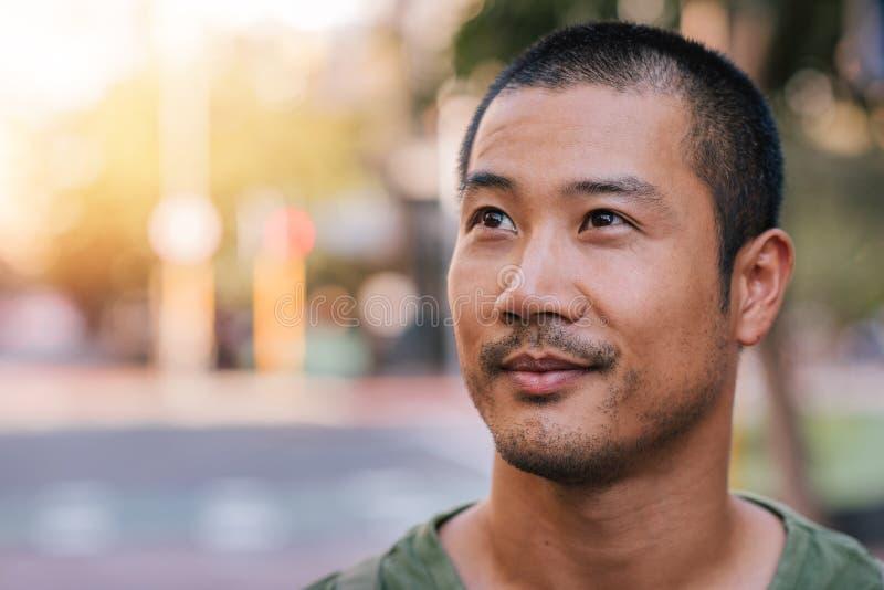 Homem asiático novo considerável que está em uma rua da cidade fotografia de stock