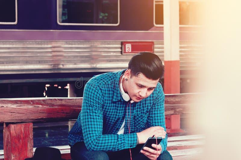 Homem asiático novo considerável que olha a música esperta do telefone e do jogo com imagem de stock royalty free