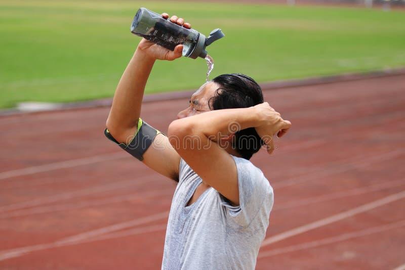 Homem asiático novo da aptidão que espirra a água em sua cara após a corrida na trilha do estádio fotografia de stock