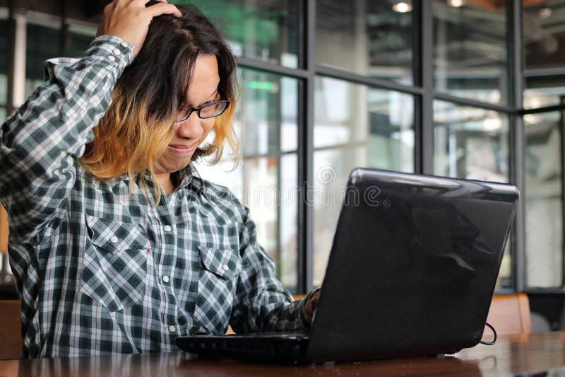 Homem asiático novo deprimido esgotado na roupa ocasional que olha o portátil no escritório imagem de stock