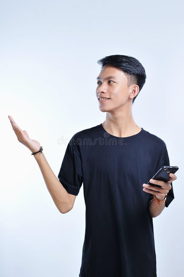 Homem asiático novo do estudante que guarda um telefone esperto e uma palma aberta da mão de lado, apresentando ao copyspace fotos de stock royalty free