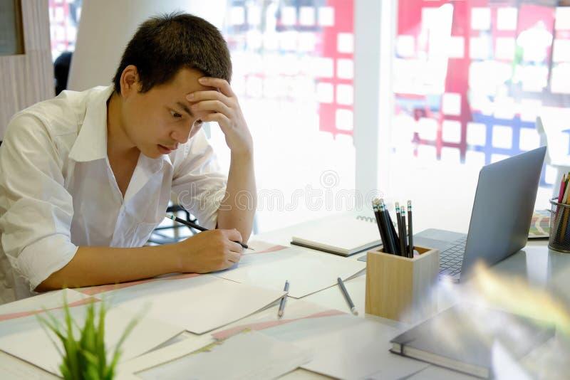 Homem asiático novo esgotado e o seu trabalho imagens de stock