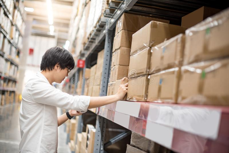 Homem asiático novo que escolhe o produto no armazém foto de stock royalty free