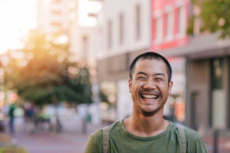 Homem asiático novo que está em um riso da rua da cidade imagens de stock royalty free