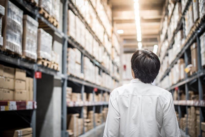Homem asiático novo que está no armazém que escolhe que comprar foto de stock