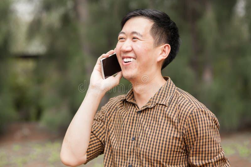Homem asiático novo que fala e que ri no telefone fotografia de stock royalty free