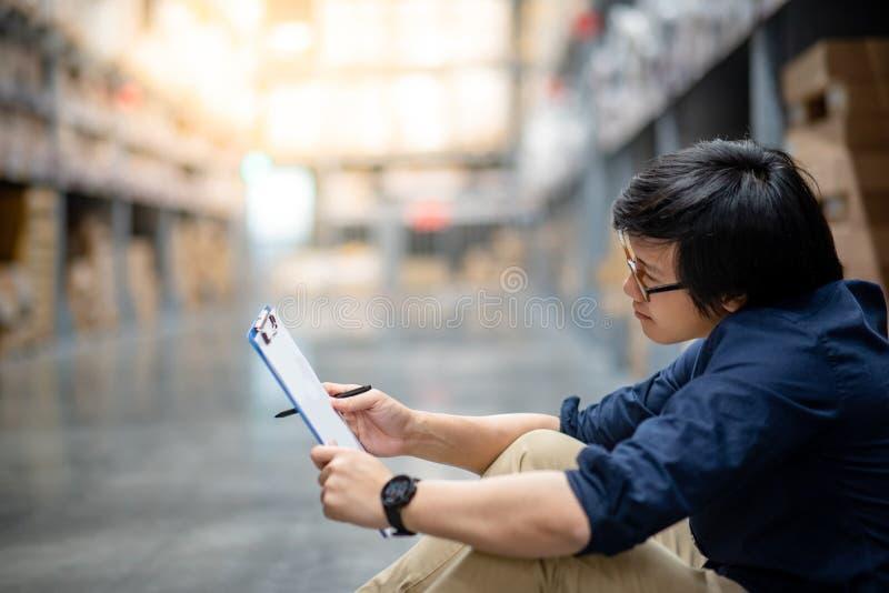 Homem asiático novo que faz a avaliação no armazém fotografia de stock royalty free