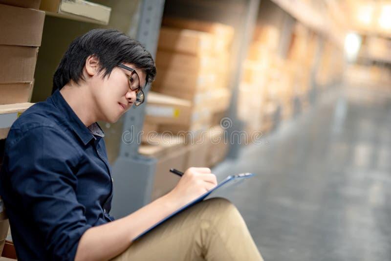 Homem asiático novo que faz a avaliação no armazém fotos de stock