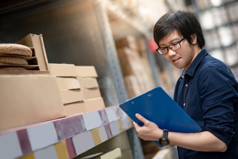 Homem asiático novo que faz a avaliação no armazém foto de stock royalty free
