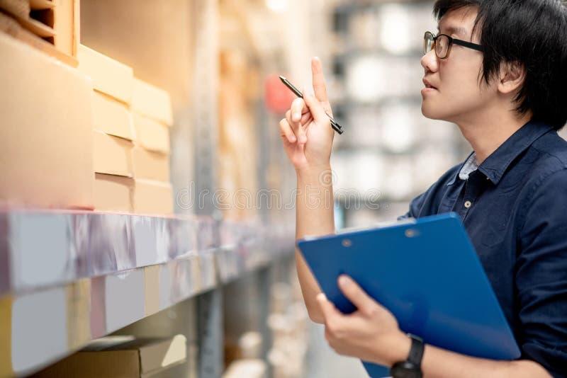 Homem asiático novo que faz a avaliação no armazém imagens de stock