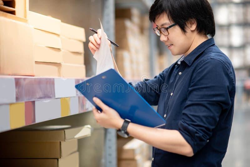 Homem asiático novo que faz a avaliação no armazém imagens de stock royalty free