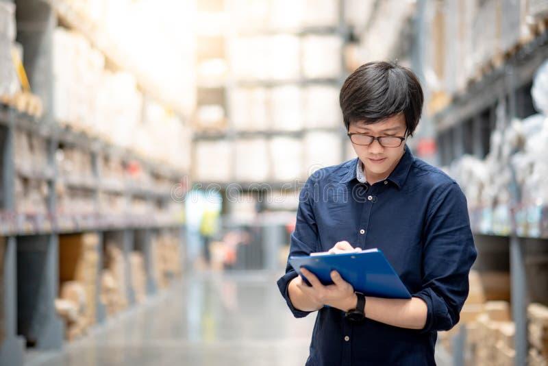 Homem asiático novo que faz a avaliação no armazém imagem de stock