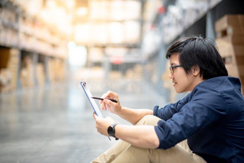 Homem asiático novo que faz a avaliação no armazém fotografia de stock