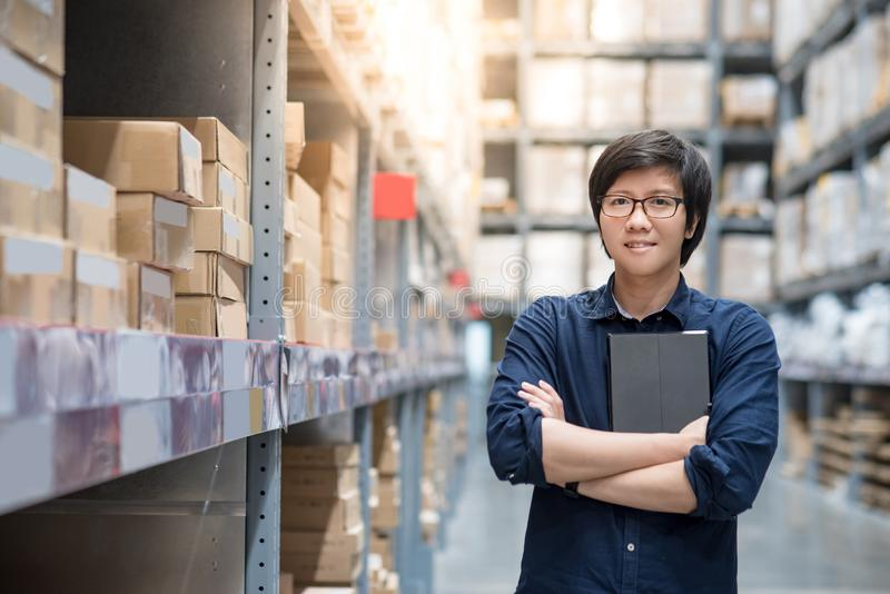 Homem asiático novo que faz a avaliação usando a tabuleta no armazém imagens de stock