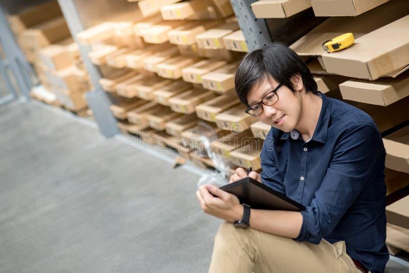 Homem asiático novo que faz a avaliação usando a tabuleta no armazém fotografia de stock