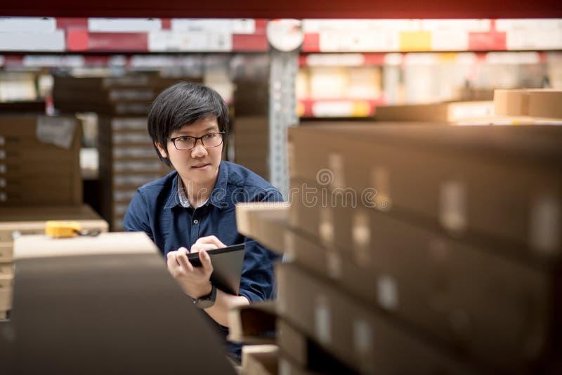Homem asiático novo que faz a avaliação usando a tabuleta no armazém imagem de stock