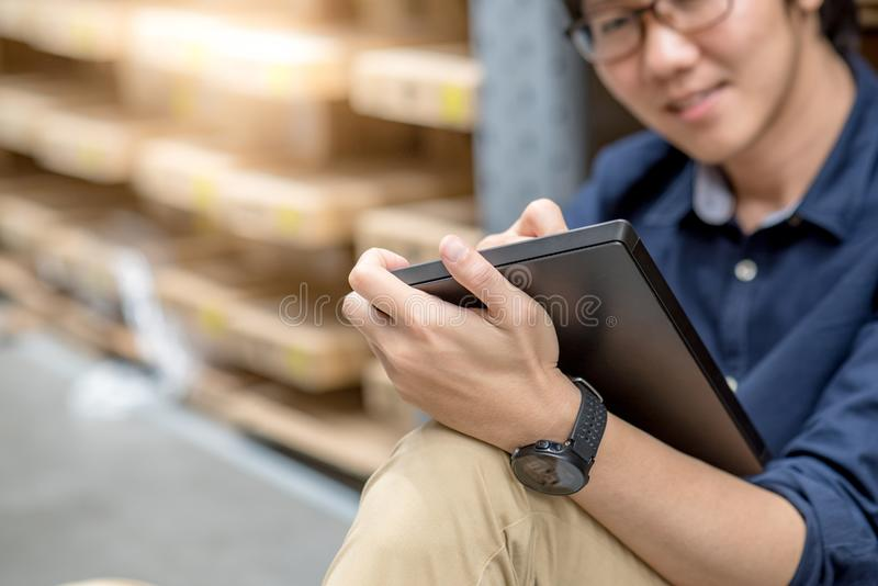 Homem asiático novo que faz a avaliação usando a tabuleta no armazém imagem de stock royalty free