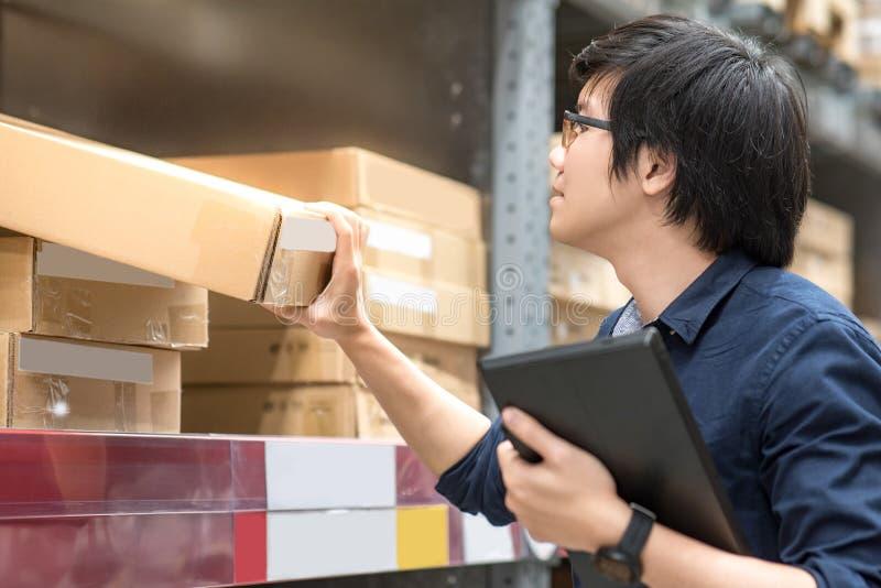 Homem asiático novo que faz a avaliação usando a tabuleta no armazém foto de stock