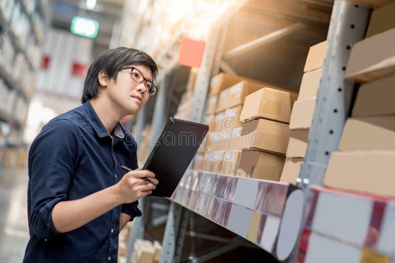Homem asiático novo que faz a avaliação usando a tabuleta no armazém fotos de stock royalty free