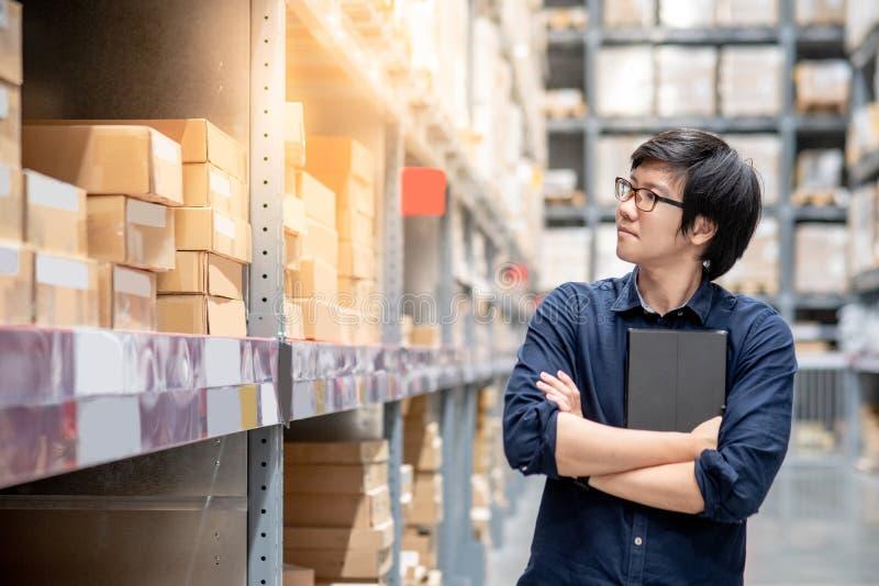 Homem asiático novo que faz a avaliação usando a tabuleta no armazém fotos de stock