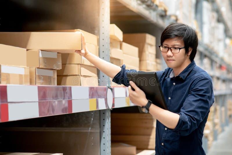 Homem asiático novo que faz a avaliação usando a tabuleta no armazém foto de stock royalty free