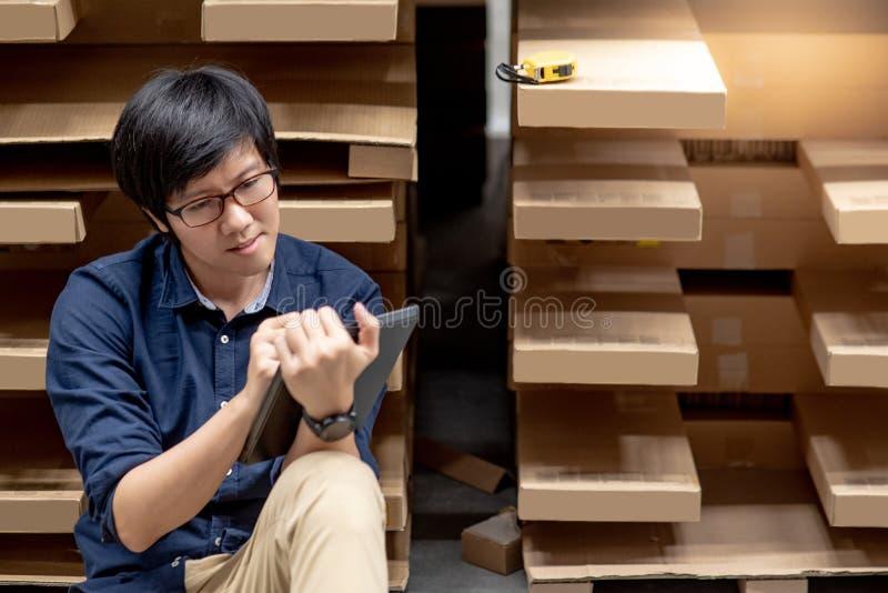 Homem asiático novo que faz a avaliação usando a tabuleta no armazém imagens de stock royalty free