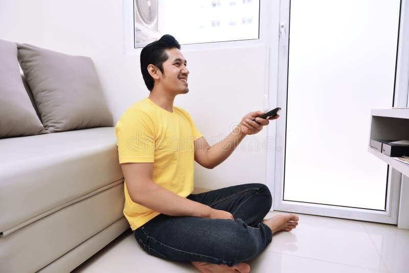 Homem asiático novo que guarda o controlo a distância que olha a tevê ao sentar-se foto de stock