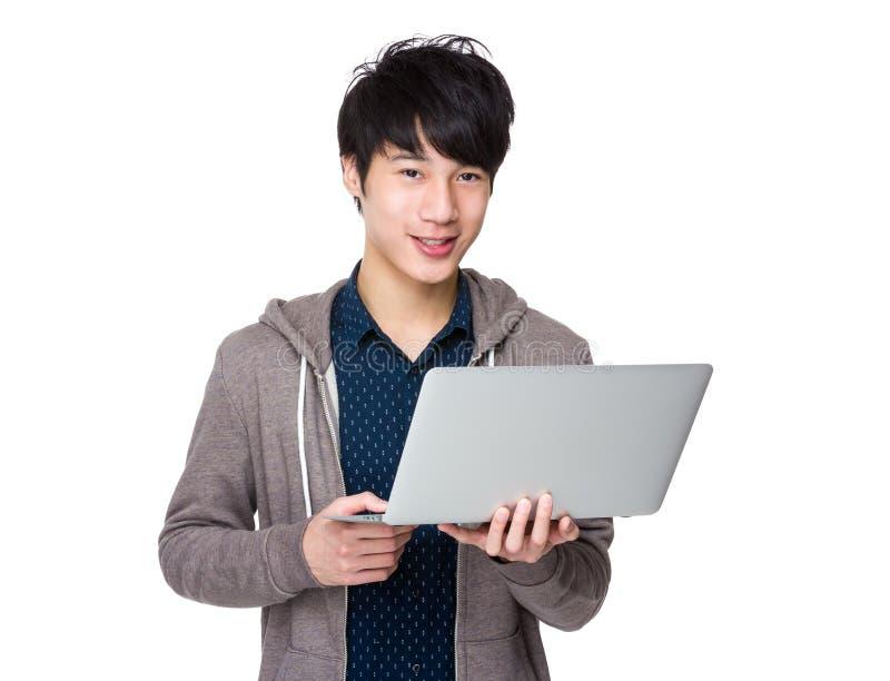 Homem asiático novo que guarda o laptop e o trabalho fotos de stock royalty free