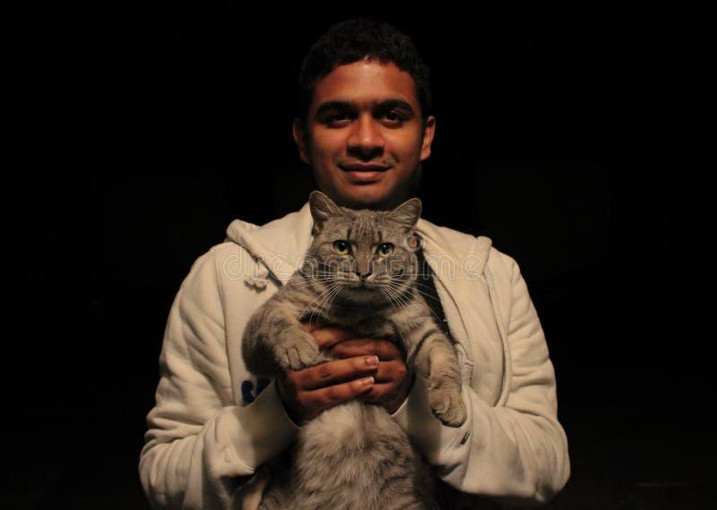 Homem asiático novo que guarda um gato com o amor e o sorriso, olhando a câmera com fundo preto liso imagem de stock