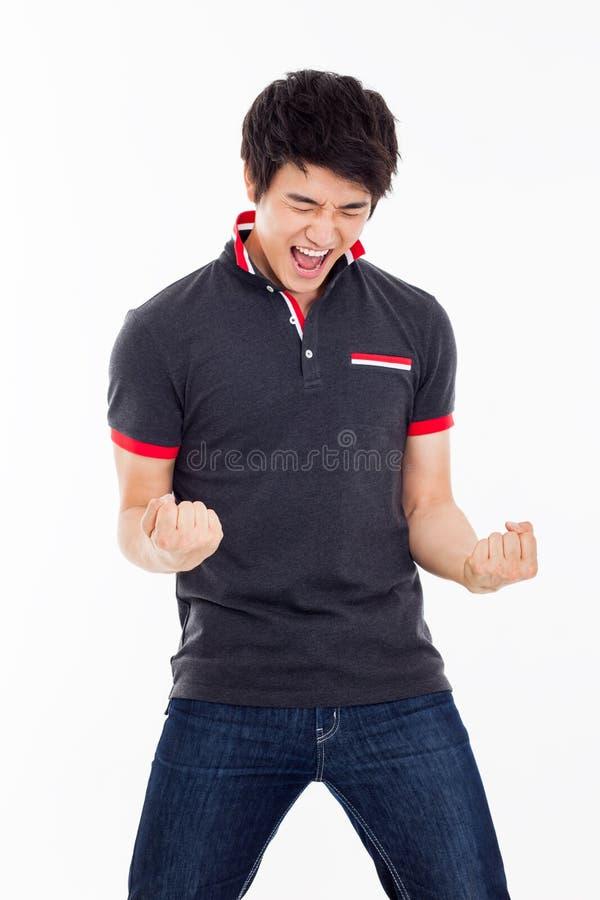 Homem asiático novo que mostra o punho e o sinal feliz. foto de stock