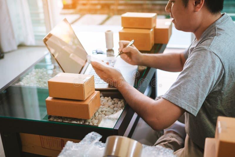 Homem asiático novo que olha no portátil do computador e que redige a lista no papel, conceito da ordem do SME imagens de stock royalty free