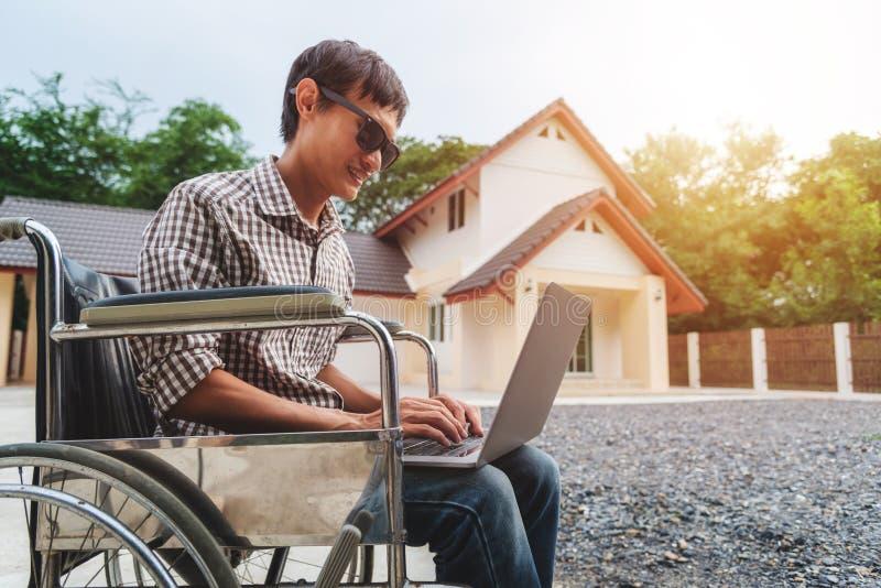 Homem asiático novo que senta-se em uma cadeira de rodas e que trabalha em seu portátil foto de stock
