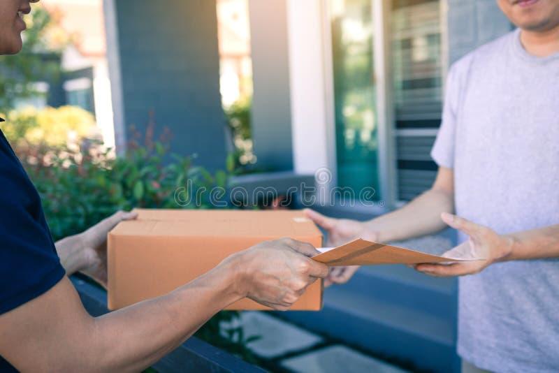 Homem asiático novo que sorri ao entregar uma caixa de cartão ao documento da terra arrendada da mulher à assinatura de assinatur foto de stock