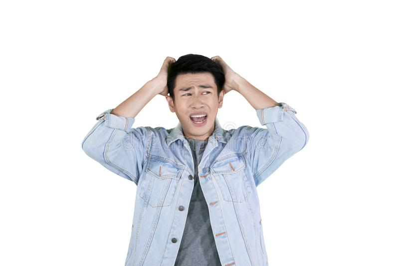 Homem asiático novo que tem a dor de cabeça no estúdio fotografia de stock